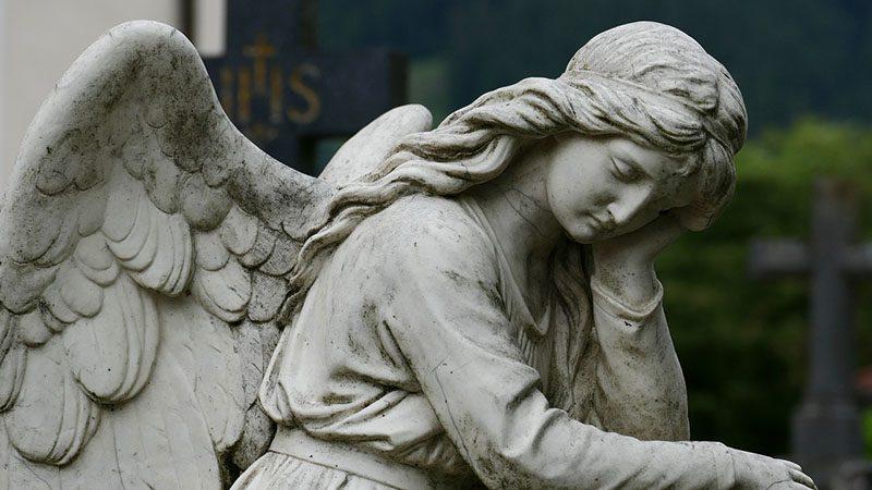 頬に手を当て悩んでいる天使の像