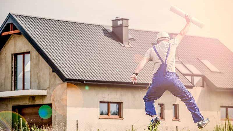 家の前でガッツポーズをする男